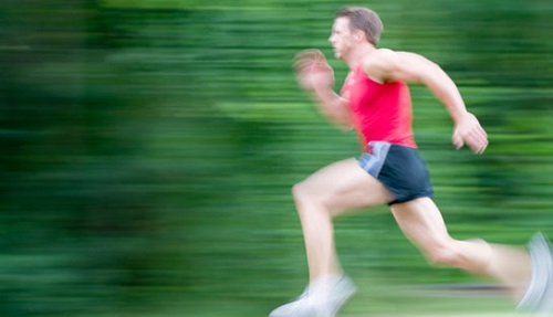 Young man running, slow shutter speed, motion blur