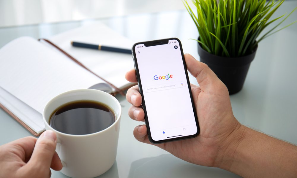 Person holding iPhone searching Google with coffee