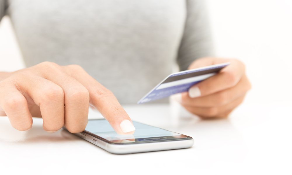 Woman Holding Credit Card Using Iphone