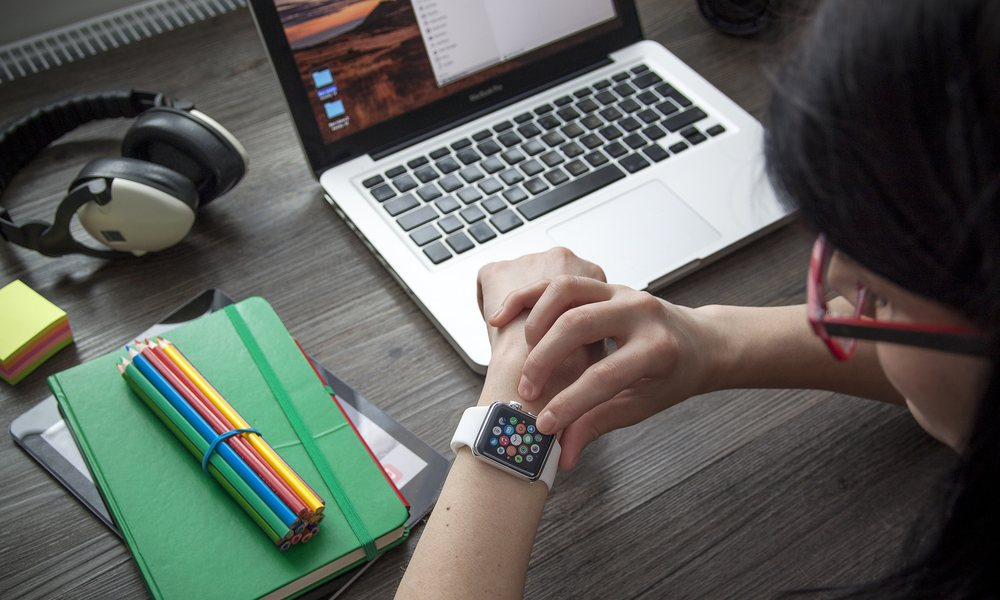 Woman Using Apple Watch At Desk With Macbook