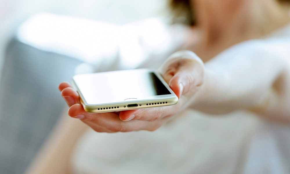 Woman Holding an iPhone with a Lightning Port