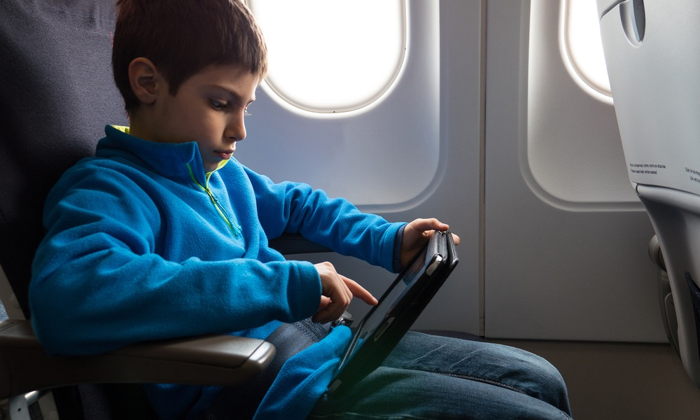 Kid Using an iPad on the Plane