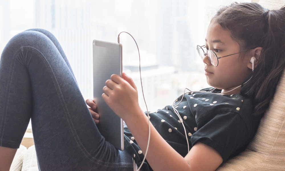 Kid Reading on an iPad with Headphones in