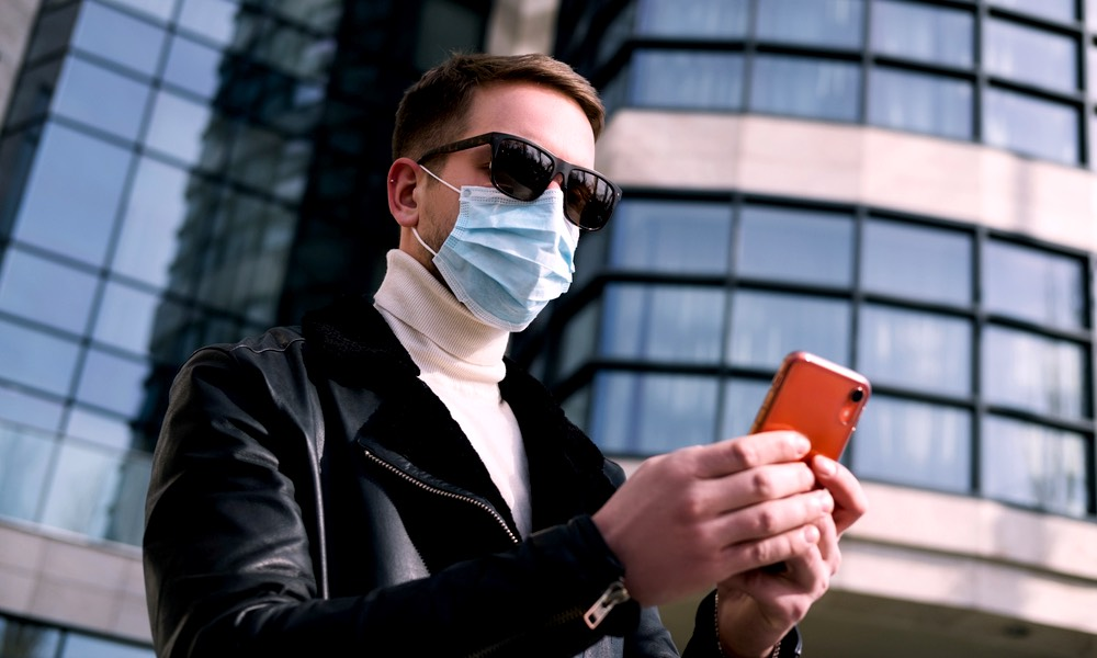 Man Using iPhone Wearing a Mask