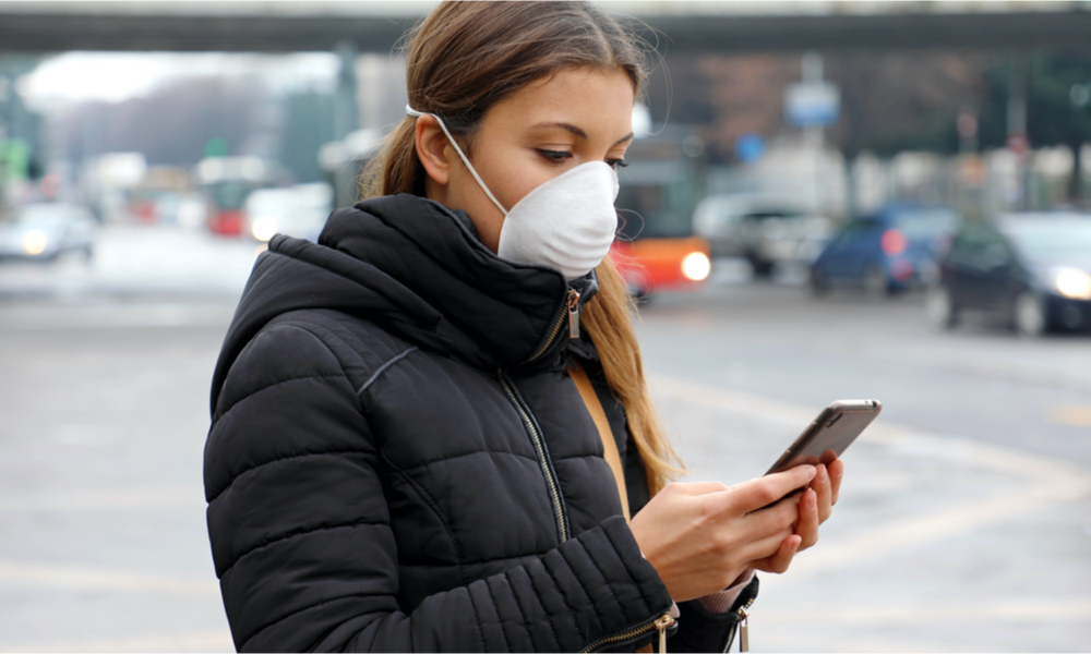 Woman wearing mask and holding iPhone