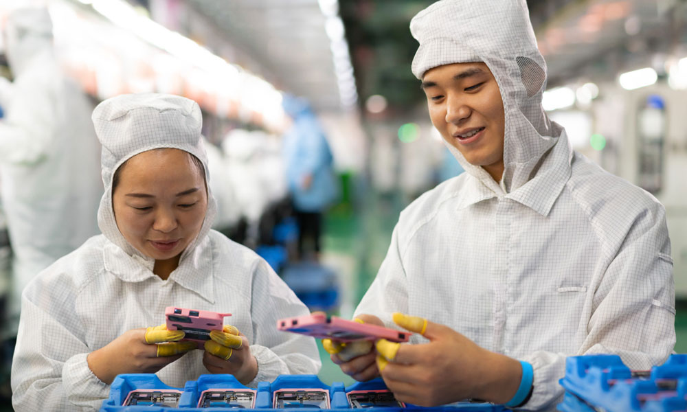 Chinese factory workers inspecting rear iPhone casings