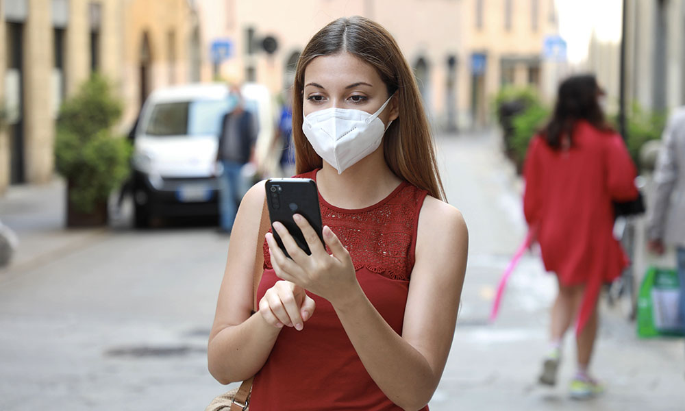 Woman in red on street wearing mask using iPhone