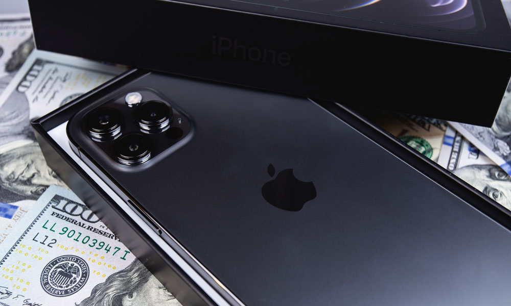 iPhone 12 Pro in box on top of money cash