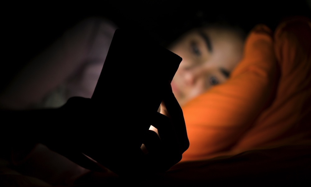 Woman Using Smartphone in Bed